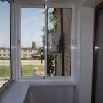 Внутри балкон обшит белыми глянцевыми панелями