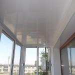 Потолок балкона обшит белыми глянцевыми панелями